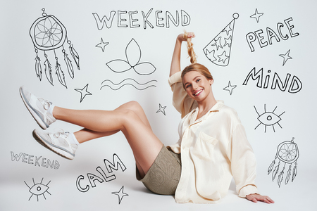 Happy and free. Full length of cute blonde woman smiling and playing with her hair tail while sitting on the floor against grey background with hand drawn doodles on it. Positive emotions. Weekend. Re