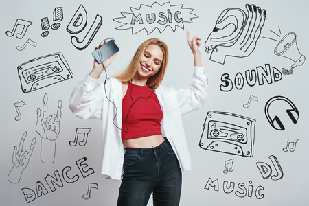 Time for music. Close up portrait of young woman in casual wear listening music with her smart phone, dancing and smiling while standing against grey background with music theme doodles. Music concept. Party 版權商用圖片