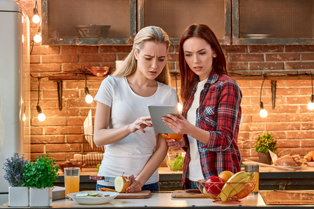 Portrait of two attractive women, having fun, while preparing fruit salad. They are fully involved in the process. Blonde girl in white T-shirt and her dark-haired friend in checkered shirt searching  写真素材