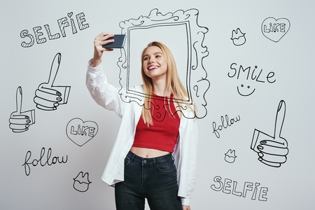 I love selfie! Cute young woman with blond hair making selfie by her smartphone and smilingwhile standing against grey background with different hand drawn doodle illustrations on it. Digital concept. Social media