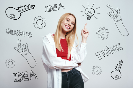 Great idea! Pretty blonde woman with long hair pointing pointing at lightbulb while standing against grey background with hand drawn doodles on it. Insights. Inspiration concept