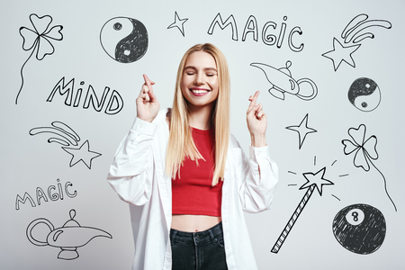 Waiting for special moment. Close up portrait of pretty blonde woman with closed eyes crossing fingers while standing against grey background with hand drawn magic tools on it. Magic concept. Mystery