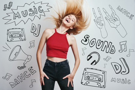 Feeling the freedom. Elegant and charming woman with long blond hair keeping eyes closed and smiling while standing against grey background with music theme doodles. Music concept. Party Stock Photo - 127042273