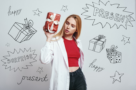 What is inside? Attractive young woman is holding a gift box and trying to guess what is inside while standing against grey background with different themed doodle illustrations on it. Holidays. Birthday concept