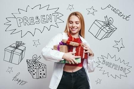 Its for me? Studio close-up portrait of happy blonde woman holding gift boxes and smiling while standing against grey background with different themed doodle illustrations on it. Birthday concept