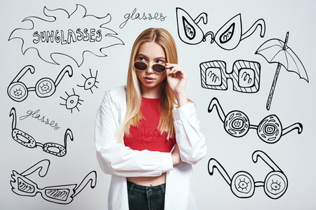 Fashion girl. Close up portrait of attractive asian woman adjusting her sunglasses and looking at camera while standing against grey background with hand drawn doodles on it. Fashion look. Beauty concept Фото со стока