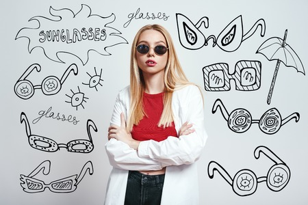 Beauty in everything. Young and stylish blonde woman in sunglasses with crossed arms looking at camera while standing against grey background with hand drawn doodles on it. Fashion look. Beauty concept