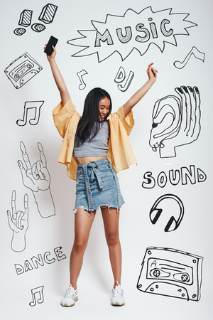 Dance! Full length portrait of pretty asian woman in casual wear holding smartphone in one hand and dancing while standing against grey background with music theme doodles. Music concept. Party concept