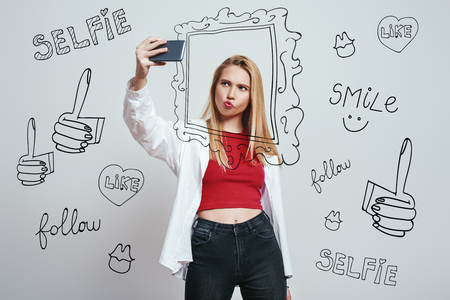 Selfie time! Pretty young woman with long hair making selfie by her smartphone and making a grimace while standing against grey background with different hand drawn doodle illustrations. Social media. Photography