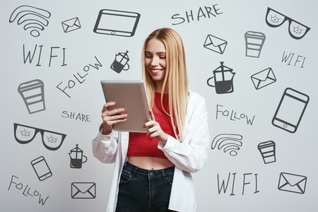 Chatting with friends. Cute blonde woman in a casual wear is using her digital tablet and smiling while standing against grey background with different doodle illustrations on it. Digital concept. Modern technology Stock fotó