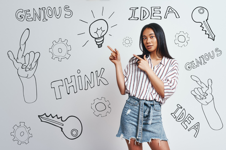 I have great idea! Cute asian woman with long hair pointing at lightbulb while standing against grey background with hand drawn doodles on it. Idea concept. Thinking process Stock fotó