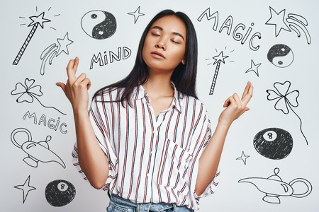 Magic in the air. Portrait of dreamy asian young woman in casual wear crossing fingers while standing against grey background with hand drawn magic tools on it. Wishness concept. Magic equipment. Mystery