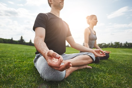 Yoga class. Young couple are meditating and doing yoga exercises while sitting in lotus pose on a green grass in open field. Sunny morning. Meditation concept. Yoga concept. Healthy lifestyle Archivio Fotografico