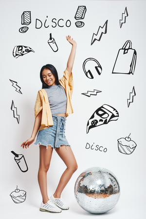 Party girl. Full length portrait of pretty asian woman standing with one raised hand near silver disco ball and smiling against grey background with different doodle illustrations on it. Music concept. Disco. Dancing.