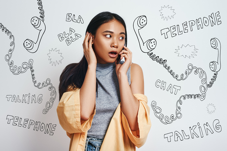 Oh my God! Close up portrait of surprised asian woman in casual wear talking on her smart phone while standing against grey background with different doodle illustrations on it. Human emotions. Shocking News
