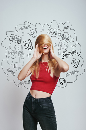 Playful mood. Cheerful young woman in red tank top covering face with her hair while standing against grey background with music theme doodles. Music concept. DJ party Stock Photo