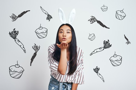 Catch! Close up of cute young Asian woman in bunny ears and casual clothes blowing a kiss while standing against grey background with hand drawn carrots and cupcakes on it. Positive emotions. Easter bunny costume