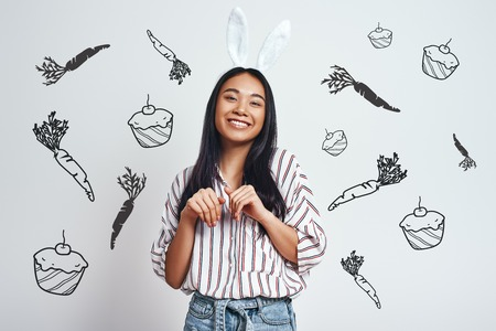 Cuter than any bunny. Attrative young asian woman in bunny ears is smiling while standing against grey background with hand drawn carrots and cupcakes on it. Happiness concept. Positive emotions. Easter bunny costume 版權商用圖片