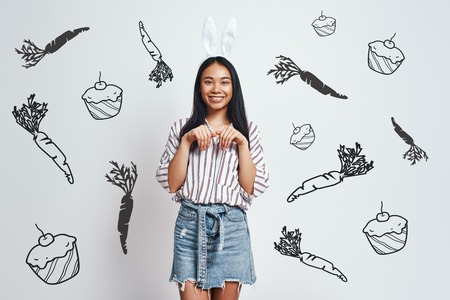 Funny bunny. Cute young Asian woman in bunny ears and casual wear is smiling while standing against grey background with hand drawn carrots and cupcakes on it. Art work. Easter party 版權商用圖片