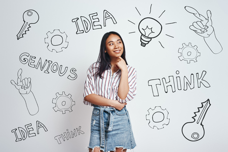 What if... Curious asian young woman in casual wear is smiling, touching her chin and and looking at drawn light bulb while standing against grey background with hand drawn doodles on it. Thinking concept. Idea concept