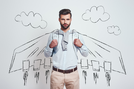 I am superhero. Confident and handsome man wearing a drawn flying cape against grey background with illustration of the clouds on it. Success concept Stock fotó