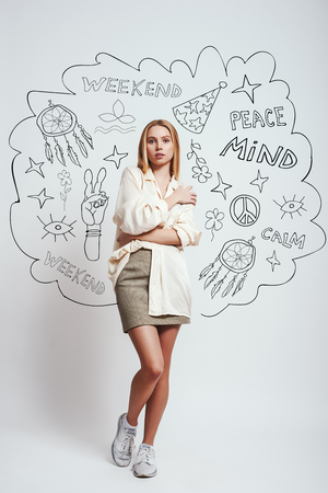 Feeling comfortable and calm...Young charming blonde woman in casual wear is looking at camera with crossed arms while standing against grey background with hand drawn doodles. Weekend. Relax concept Stock fotó