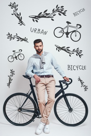 Enjoying urban lifestyle. Full length of stylish young man leaning on his bicycle against grey background with hand drawn doodles on it. Urban style. City life