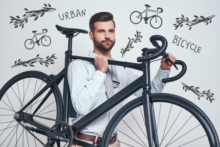 Best transport. Close up photo of good looking man in casual clothes carrying his bicycle while standing against grey background with hand drawn doodles on it. Urban style. City life