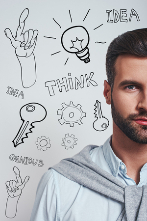 Full of ideas. Vertical half face portrait of a confident bearded man in blue shirt looking at camera while standing against grey background with different doodle illustrations on it. Thinking process