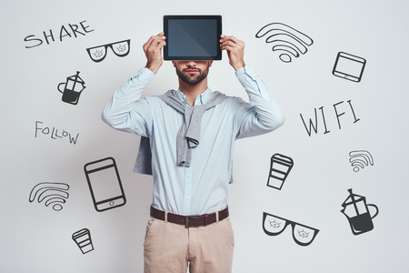 My assistant in any cases. Bearded man in casual clothes is holding his digital tablet in front of his head while standing against grey background with different doodle illustrations on it. Digital concept. Social media