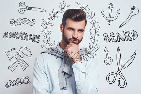 Confident in his beauty.. Charming young man holding his hand on a chin and thinking while standing against grey background with doodles on the theme of barber shop. Men beauty. Hair care