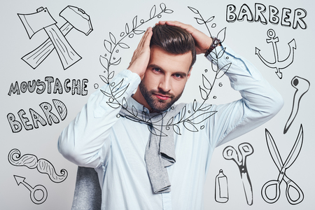 Everything must be perfect. Handsome young man keeping hands on hair and looking at camera while standing against grey background with hand drawn doodles on it. Barber shop