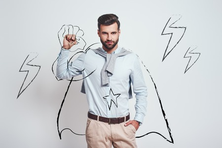 You can do it! Young attractive brunet wearing a drawn cape and raising one hand clanched in fist above his head while standing against grey background with illustration of the lightning bolts. Success concept