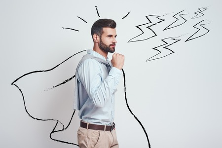I am enough strong! Confident and attractive young man wearing a drawn cape showing gesture of success while standing against grey background with illustration of the lightning bolts. Success concept 版權商用圖片