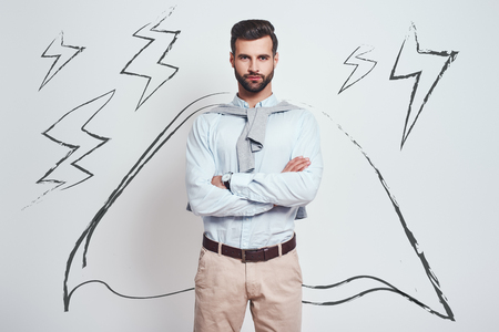 Confidence and power. Charming bearded man wearing a drawn cape with crossed arms is looking at camera while standing against grey background with illustration of the lightning bolts. Success concept. Superhero concept Stok Fotoğraf