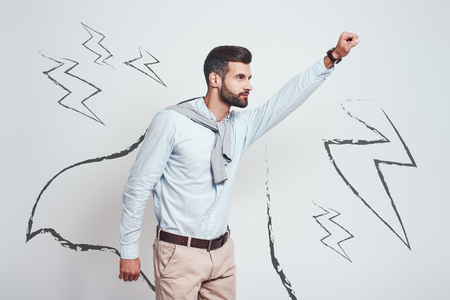 Like a hero. Young bearded man wearing a drawn cape and raising his one hand up while standing against grey background with illustration of the lightning bolts on it. Enthusiasm concept. Success concept