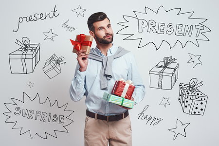 Buying gifts in advance. Good looking and smiling man is holding colorful gifts for friends while standing against grey background with different doodle illustrations on it. Holidays