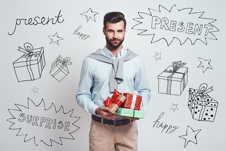 Preparing for holidays. Handsome smiling man is holding gifts for friends while standing against grey background with different doodle illustrations on it. Birthday concept Фото со стока