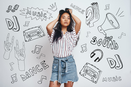 In love with music. Portrait of gorgeous asian woman touching her long hair and looking at camera while standing against grey background with music theme doodles on it. Music and dance concept