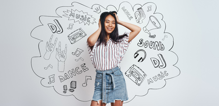 Enjoying music. Pretty smiling asian woman in casual wear playing with her hair and looking at camera while standing against grey background with music theme doodles. Music concept. Women beauty. Web banner Stock Photo