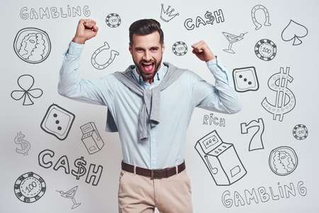 It is all mine! Happy young bearded man is celebrating his success with raised hands while standing against grey background with different doodle illustrations on it. Gambling concept. Positive emotions. Money concept.