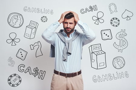 Game over. Close-up portrait of depressed young man keeping head in his hands and making a sad face against grey background with different doodle illustrations on it. Gambling concept. Human emotions