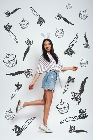 Cute bunny. Full length of attractive asian woman in bunny ears and casual wear is smiling while standing against grey background with hand drawn carrots and cupcakes on it. Positive emotions. Easter bunny costume