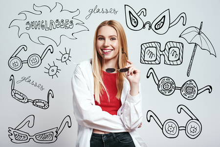 Ready for vacation. Portrait of cheerful blonde woman in casual clothes holding her sunglasses and smiling while standing against grey background with hand drawn doodles on it. Fashion concept.