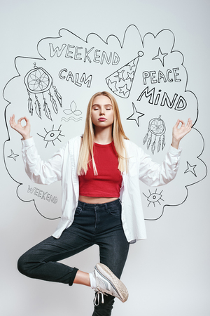 Yoga style. Attractive young woman meditating and keeping eyes closed while standing against grey background with hand drawn doodles on it. Meditation concept. Relaxation