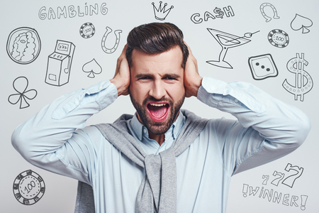 How could I loose? Young handsome man closing ears with hands and screaming while standing against grey background with different doodle illustrations on it. Gambling concept. Gamer.