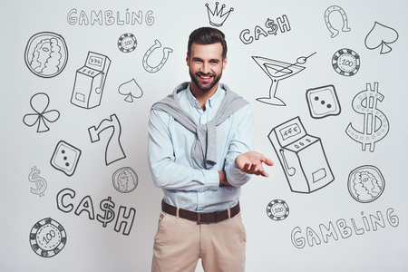 Confident in his luck. Charming bearded man in a blue shirt is smiling at camera while standing against grey background with different doodle illustrations on it. Gambling concept. Positive emotions. Money concept.