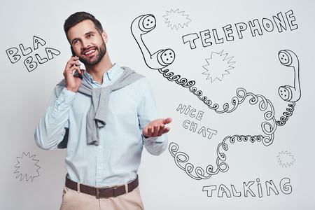 Glad to hear you! Attractive young man in casual wear is talking on the phone and smiling while standing against grey background with different doodle illustrations on it. Communication concept Banco de Imagens