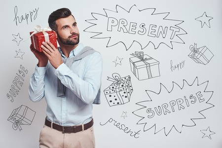 What is inside? Attractive stylish man is holding a gift box near his ear and trying to guess what is inside while standing against grey background with different doodle illustrations on it. Birthday concept
