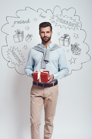 Present for you! Elegant man in casual clothes is holding a gift box and smiling at camera while standing against grey background with different doodle illustrations on it. Birthday concept